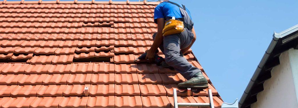 Person Getting Roof Repaired After Learning Roofing Repairs Covered by Insurance