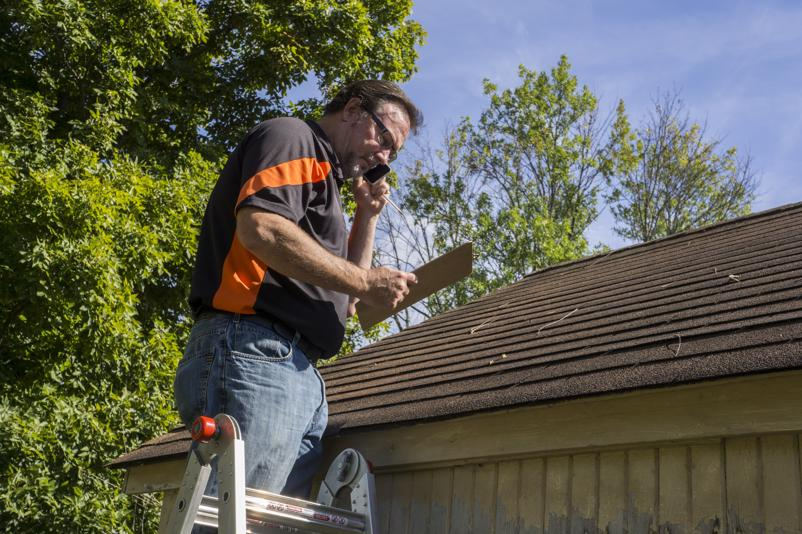 A roofing technician examining a roof for damage.