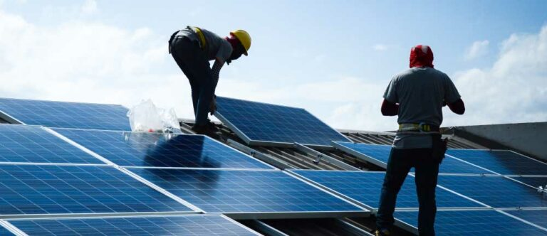 Two men installing solar panels on a roof.
